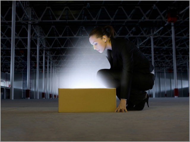Businesswoman Looking At Glowing Box In Empty Warehouse