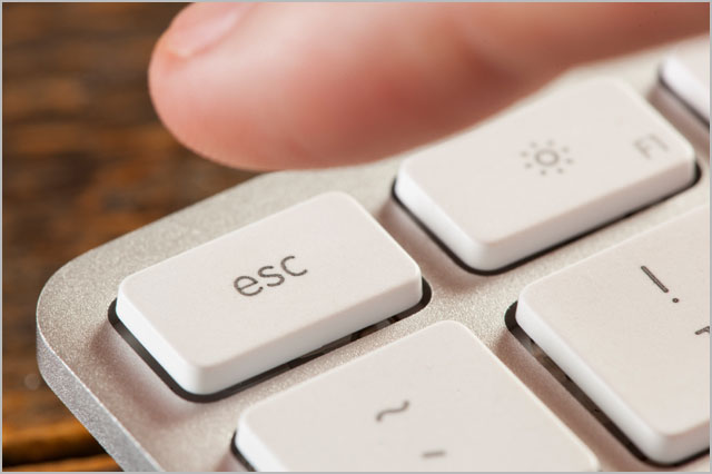 Finger Pressing Escape on a Grey Computer Keyboard